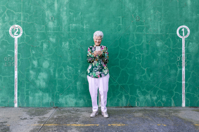 Elegant cheerful elderly female in stylish outfit standing against green wall with numbers on parking lot using mobile phone