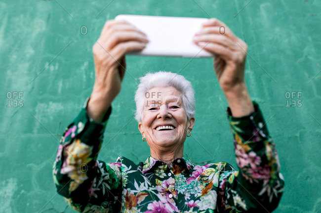 Low angle of cheerful senior female with gray hair taking self portrait on mobile phone while standing against green wall