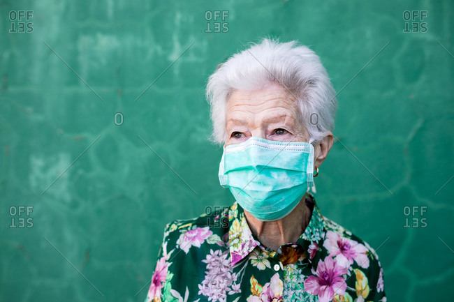 Optimistic elderly lady in stylish colorful outfit and protective mask for coronavirus prevention looking away standing against green wall
