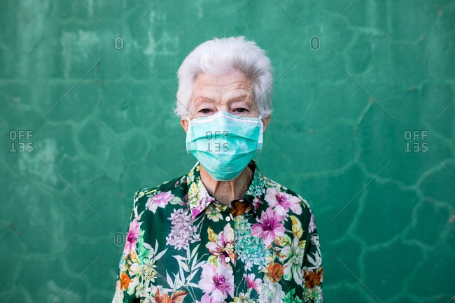 Optimistic elderly lady in stylish colorful outfit and protective mask for coronavirus prevention looking at camera standing against green wall