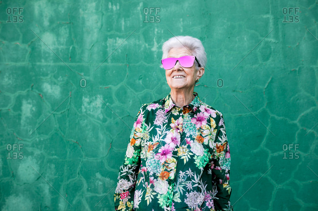 Confident senior gray haired female in stylish colorful clothes and trendy sunglasses smiling happily while standing against green wall