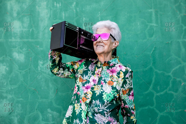 Cool elderly female in colorful trendy blouse and sunglasses carrying boom box and enjoying music against green wall