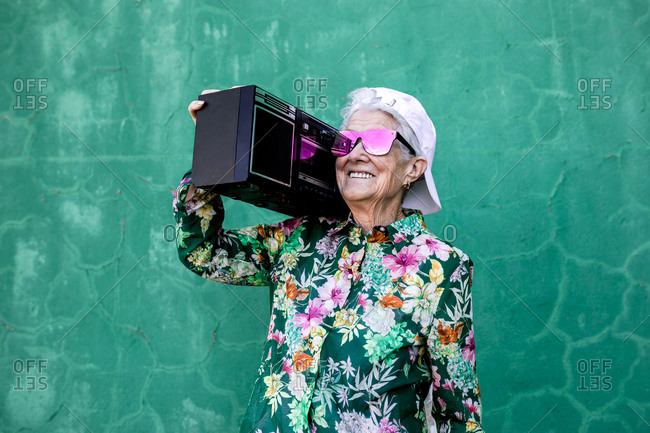 Cool elderly female in colorful blouse and trendy cap and sunglasses carrying boom box and enjoying music against green wall