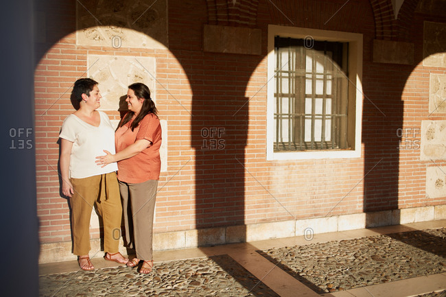Content chubby homosexual couple in casual clothes embracing near old building while looking at each other