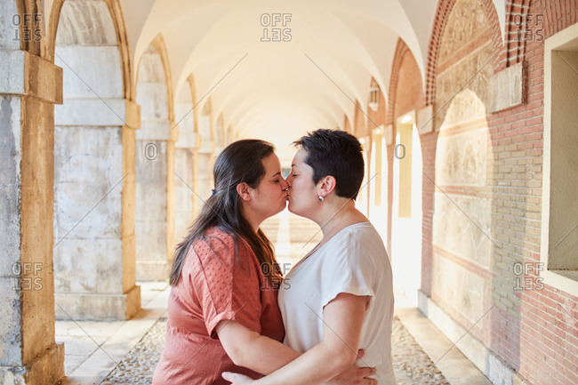 Side view of homosexual couple of women kissing with closed eyes near old arched building