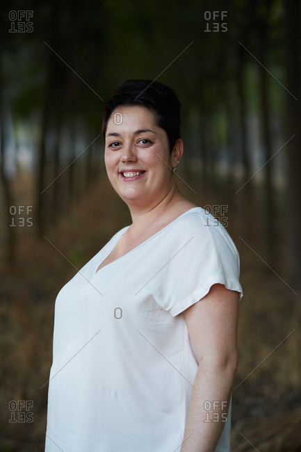 Side view of cheerful young chubby female in casual apparel looking at camera with toothy smile in daylight