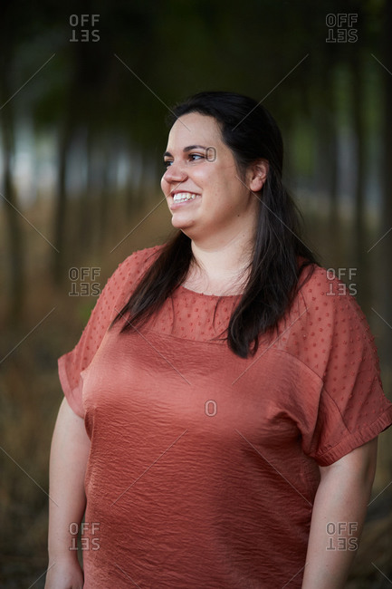Cheerful young chubby female in casual apparel looking away with toothy smile in daylight
