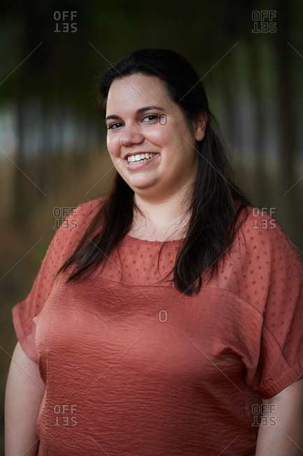 Cheerful young chubby female in casual apparel looking at camera with toothy smile in daylight