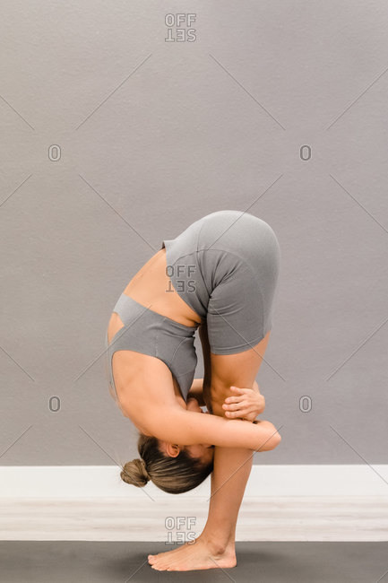 Side view of slim female in sportswear doing yoga in Uttanasana while standing on yoga mat at home