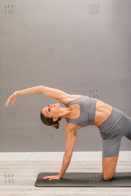 Flexible female doing yoga in Side Plank on Knee pose while practicing mindfulness on mat at home