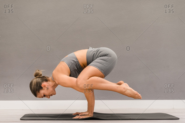 Side view of slim female in activewear balancing on hands in Bakasana and practicing yoga on mat at home