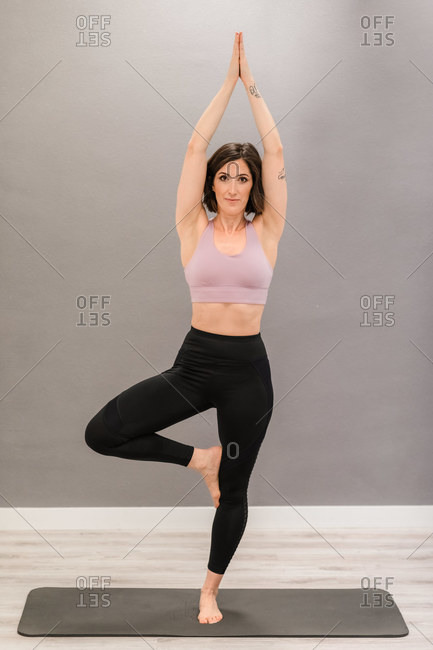 Content slender female in activewear practicing yoga in Vrksasana while balancing barefoot on mat at home and looking at camera