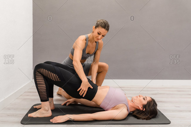 Flexible female lying on mat in Bridge pose and doing yoga with help of professional instructor during class in studio