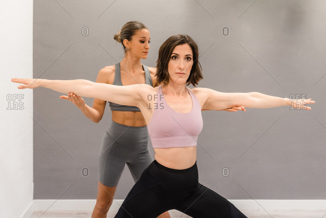 Concentrated female standing in Virabhadrasana and doing yoga with support of personal instructor in bright studio