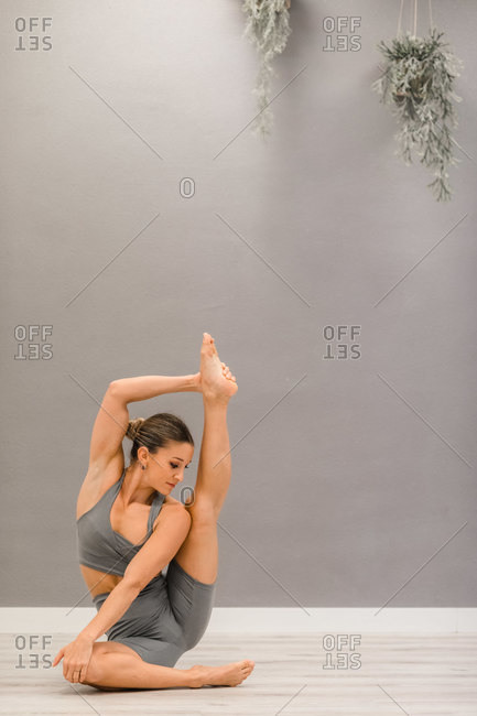 Serene female in sportswear sitting barefoot on floor and doing yoga in Krauncasana with raised leg