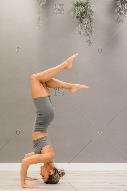 Side view of tranquil female performing headstand and balancing in Salamba Sirsasana while practicing mindfulness and doing yoga
