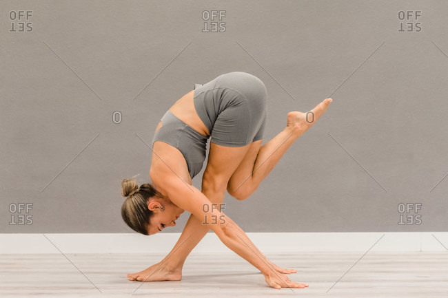 Side view of slim female in activewear balancing barefoot on leg in forward bend while doing yoga in bright studio