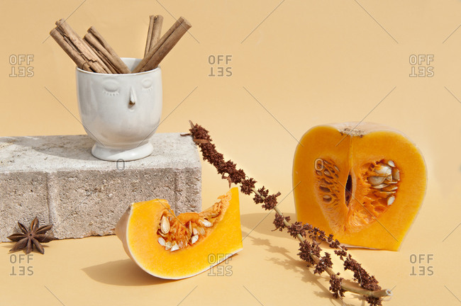 Bright ripe pumpkin with seeds near decorative vase with cinnamon pods on brick and dried anise
