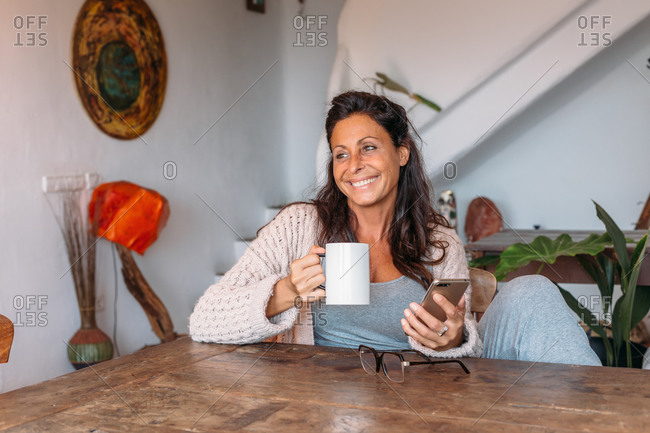Cheerful adult ethnic female in casual outfit drinking hot coffee and chatting on mobile phone while resting at wooden table in room with rustic interior