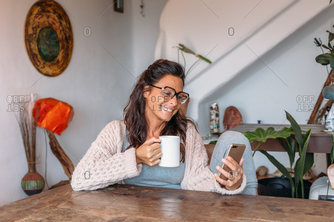 Content adult ethnic female in warm knitted wear sitting in chair and messaging on mobile phone while resting with cup of hot drink in cozy house
