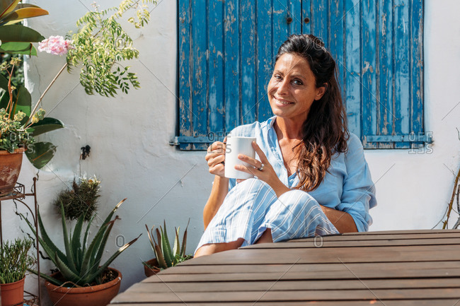 Happy adult ethnic female in casual clothes and eyeglasses enjoying cup of coffee in summer day