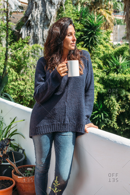 Dreamy adult ethnic female in warm knitted pullover and jeans drinking coffee and looking away thoughtfully while standing near fence on sunny terrace against green tropical plants