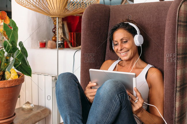 Adult ethnic female in casual clothes listening music for relaxation with tablet and headphones while sitting on comfortable chair in cozy room in country house