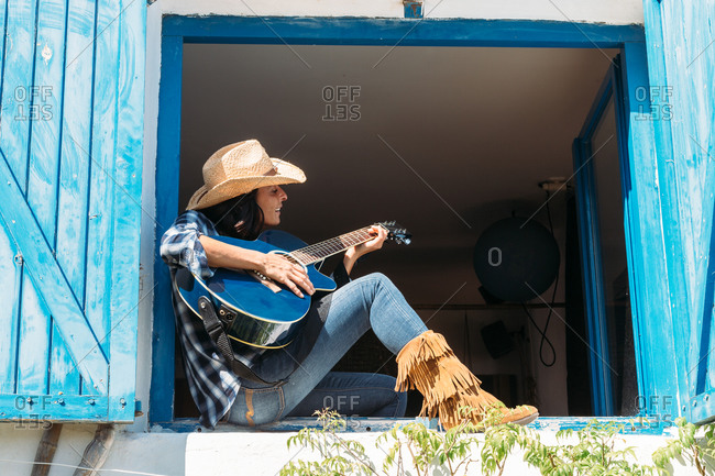 Side view of cheerful ethnic female dressed in cowboy style clothes with boots and hat sitting on windowsill and playing guitar while resting in rural house in summer day