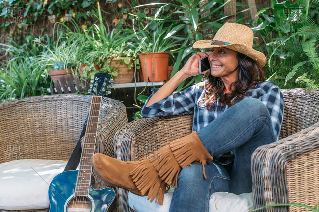 Positive adult ethnic female in stylish cowboy outfit talking on smartphone while sitting in wicker armchair near guitar on garden terrace with green potted plants