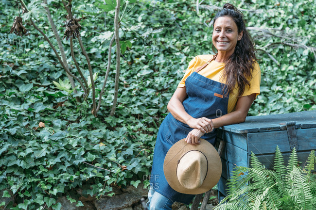 Positive adult ethnic female in denim apron and with hat in hand standing in tropical garden with green lush foliage in summer day