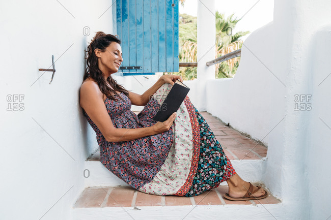Full body side view of relaxed adult ethnic female in sundress reading interesting book while sitting on steps on balcony and resting during summer holidays in tropical country