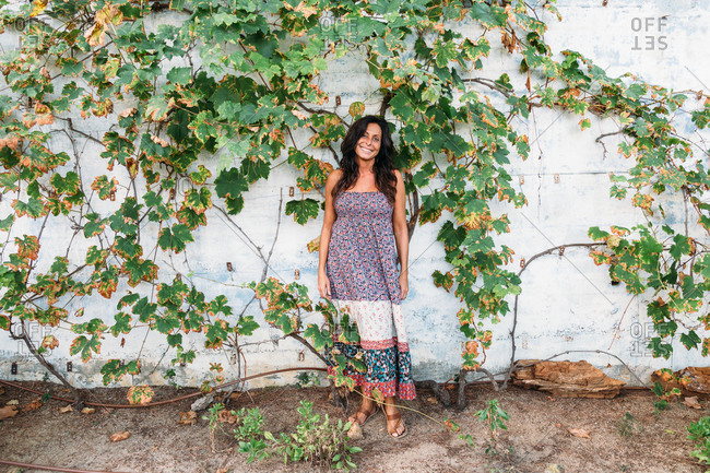 Full length of smiling adult ethnic female in casual summer dress standing against weathered stone wall with green ivy plants