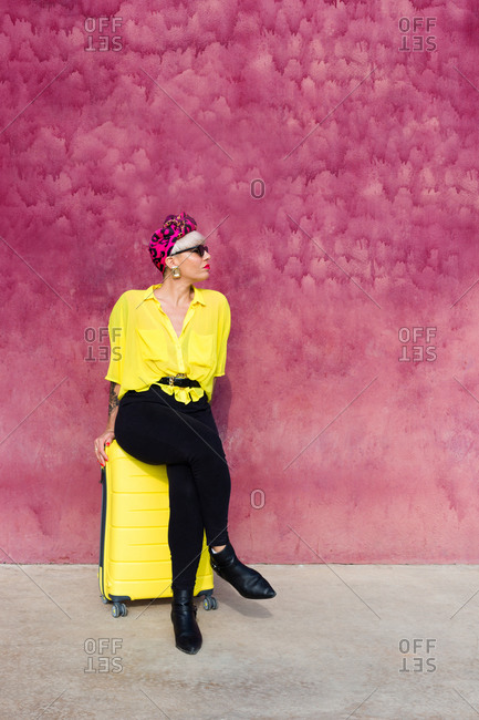 Female traveler in vibrant trendy clothes sitting on yellow suitcase near building with pink wall and looking away