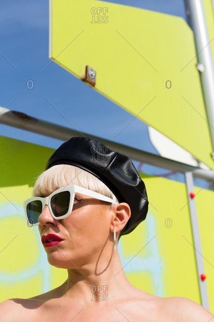 Confident female hipster in street style clothes with trendy hat and sunglasses standing in urban area of city and looking away