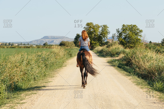 Beautiful woman riding along a country road on a sunny afternoon