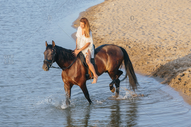 Beautiful woman in a white dress riding a horse crossing a river at sunset