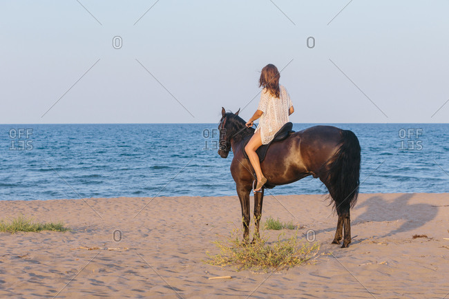 Beautiful woman in white dress riding a horse on the beach at sunset
