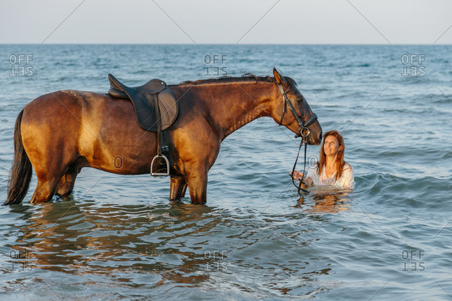 Woman in white dress bathing with her horse in the sea at sunset