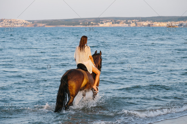 Beautiful woman in white dress riding a horse along the seashore at sunset