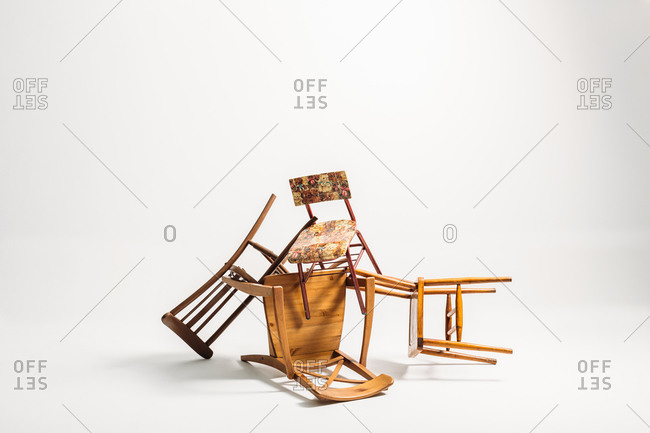 Set of old chairs stacked against white background
