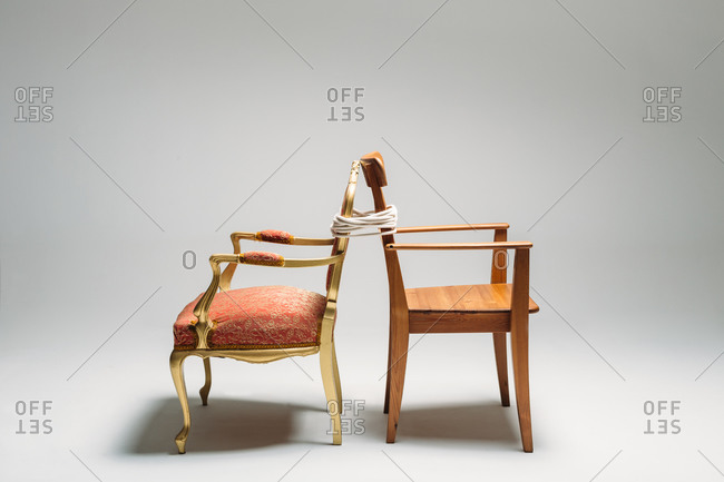Pair of classic chairs tied with rope on neutral background