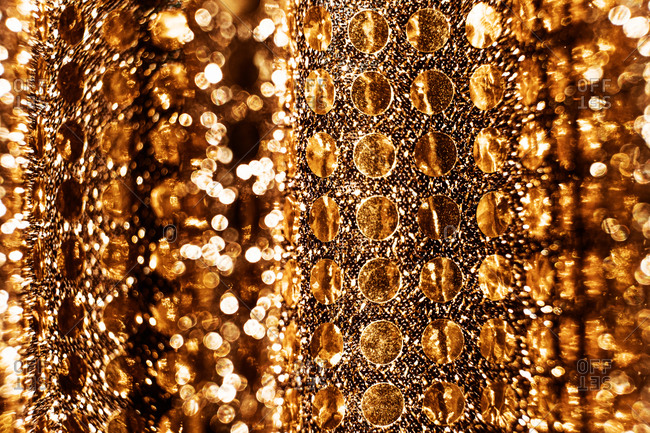 Closeup of sparkling textured surface with shiny golden round sequins for festive background