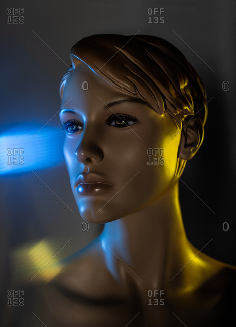 Creative image of mannequin woman in dark room with light effects