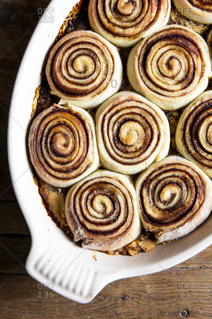 Close up overhead view of cinnamon rolls in a baking dish on a wooden table