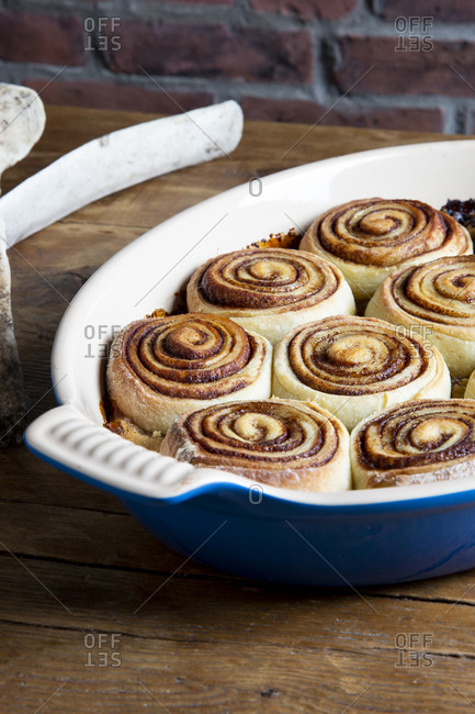 Close up of cinnamon rolls fresh out of the oven in a blue baking tray