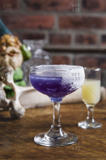 Butterfly pea flower infused rum in a purple cocktail served on a wooden table with gnome in background
