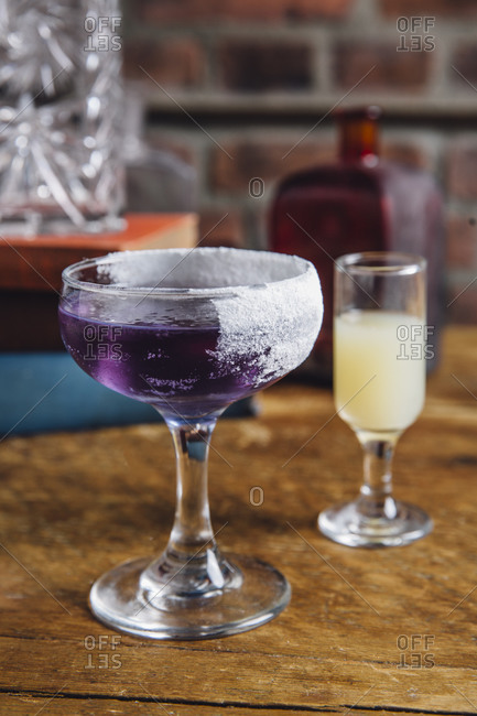 A purple cocktail with butterfly pea flower infused rum in a coupe glass served on a wooden table