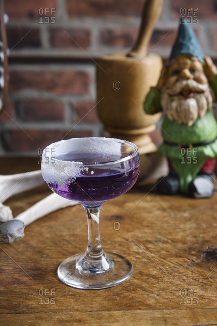 Purple cocktail with butterfly pea flower infused rum served on a wooden table with gnome in background