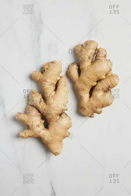Overhead view of ginger on a white marble background