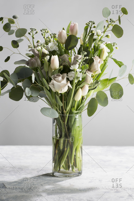 Floral arrangement in glass vase with roses and eucalyptus on a textured background